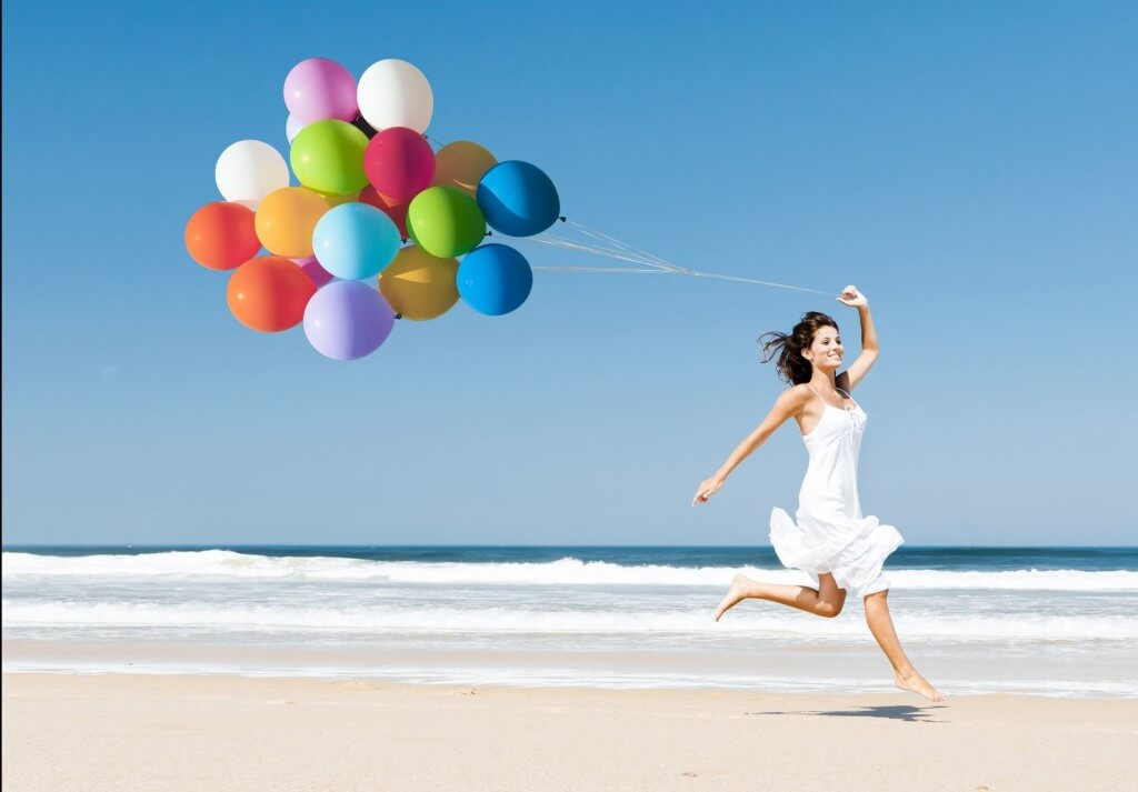 Woman balloons beach